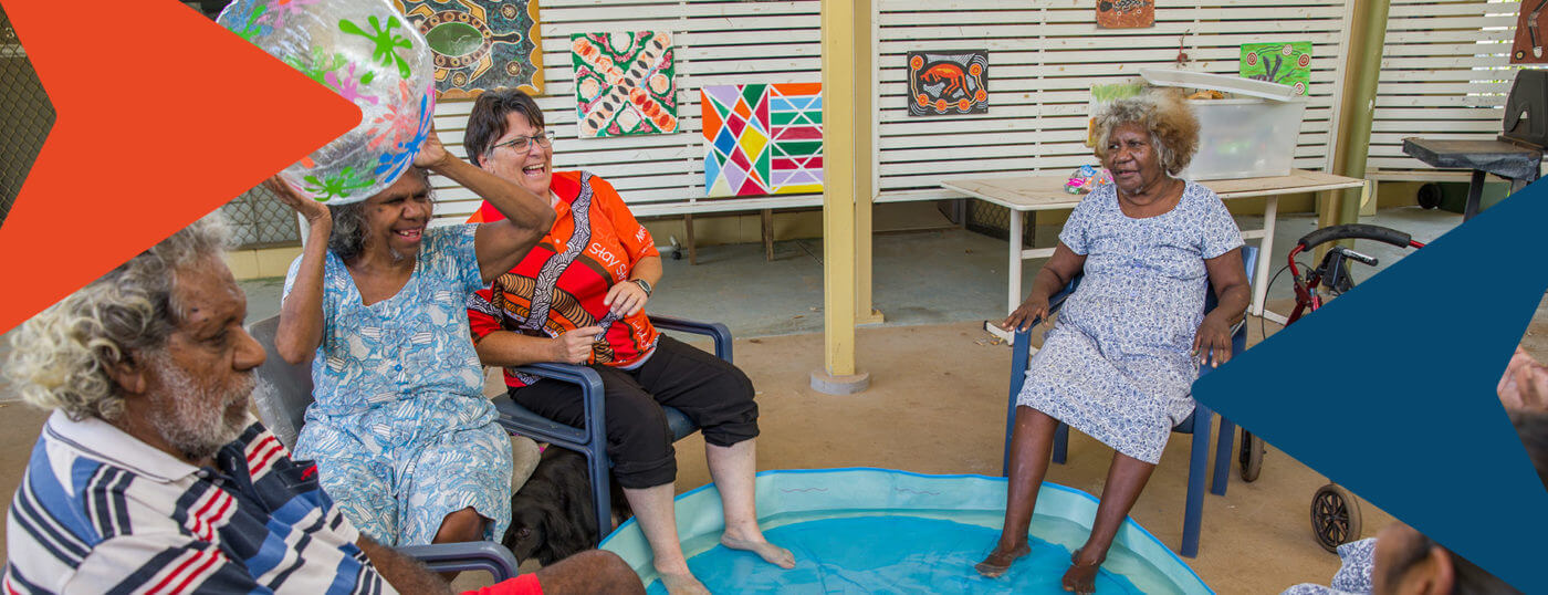 Aged care residents cooling their feel in a wading pool as they throw a beach ball around.