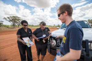 Staff explaining services to client on a dirt road to one of the many NWRH communities