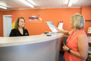 NWRH Townsville Reception greeting a client who is picking up a NWRH brochure